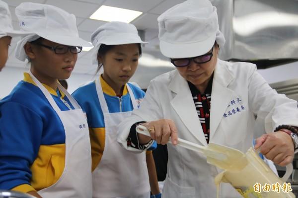 弘光科大民生院長林麗雲教小學弟妹做桂圓蛋糕 。(記者張軒哲攝)
