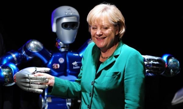 經濟學人雜誌整理出16種未來不會被機器人取代的職業;圖為德國總理梅克爾,2010年參加航太展與機器人握手畫面。(法新社)