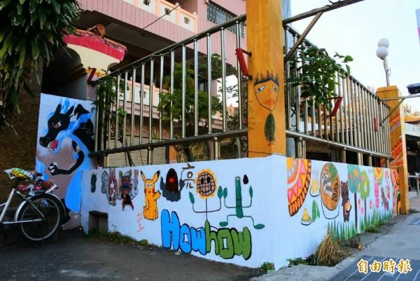 南市南區南寧高中學生利用萬年殿前的公車站牌圍牆完成社區彩繪大畫作。(記者王俊忠攝)