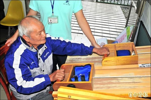 卓溪鄉70歲阿公因下半身行動不便,為增強上半身肌力,復健師讓他做推沙包運動。(記者花孟璟攝)