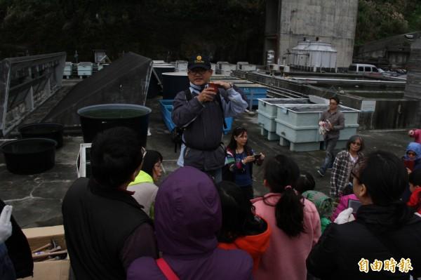 八里垃圾掩埋場技工李舜傑向親子們說明種植台灣百合的技巧。(記者林欣漢攝)