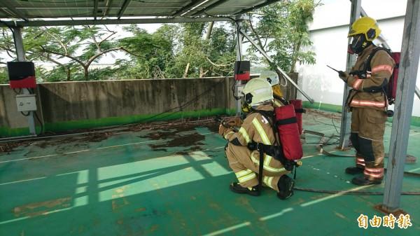 新營消防員抵達裝設太陽能板的屋頂,就定位演練。(記者楊金城攝)