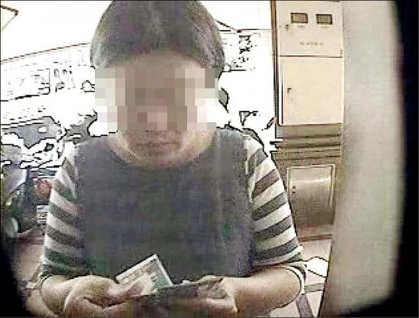 李女被拍到在提款機前領錢。(記者姚岳宏翻攝)