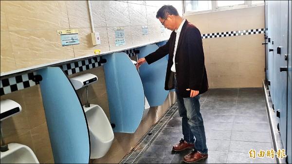 東中校長張瑞杰檢視廁所發臭源頭。(記者黃明堂攝)