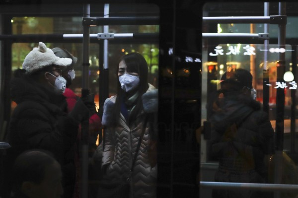 中國各地受到霧霾所擾,圖為中國北京乘客帶著口罩搭乘公車。(美聯社)