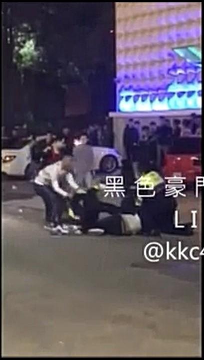 洪姓男子(白衣)從背後將員警拉開,隨後繼續攻擊倒地的酒客。(翻攝臉書黑色豪門企業)