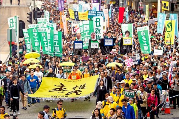 香港民間人權陣線元旦發起「主權在民」遊行,近萬人上街要求港府撤回四名議員的司法覆核案,並對中國全國人民代表大會釋法表達不滿,要求特首真普選。(歐新社)