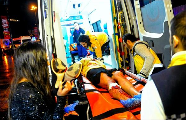 醫護人員將一名在伊斯坦堡夜店恐攻事件中受傷的民眾送上救護車。 (美聯社)