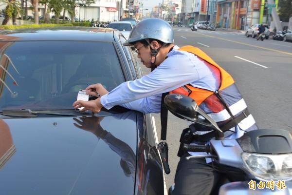 彰化市路邊停車收費今天上路,收費員穿梭市區開出收費單。(記者湯世名攝)