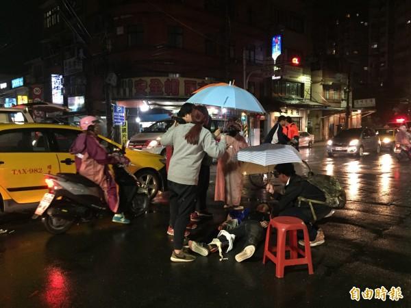 路過的民眾與附近的店家,紛紛拿傘幫倒地的騎士擋雨,令人感到暖心。(記者吳昇儒攝)