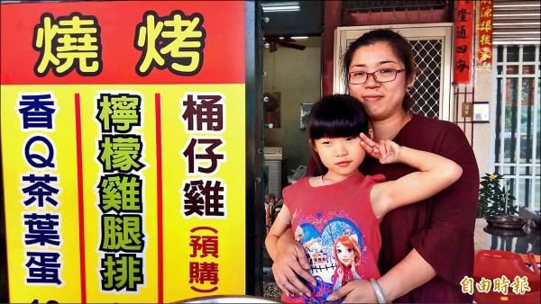 8歲女童晴雯(前)不僅勇敢面對燙傷,還貼心幫媽媽(後)賣桶仔雞。(記者洪定宏攝)