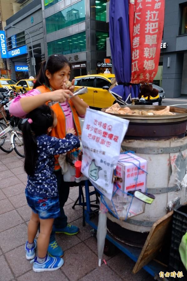 地瓜媽媽小玲(右),下午賣到一半攤車放著就去接女兒(左)下課,然後賣到晚間六、七點才回家,而跟其他地瓜媽媽的孩子一樣,都已練就出一身叫賣地瓜本領。(記者陳炳宏攝)
