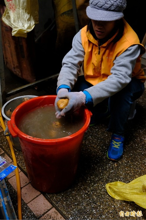 地瓜媽媽小玲,因為洗地瓜機器故障,即使天冷,一早送孩子去上課後,立即忙著洗地瓜。 (記者陳炳宏攝)