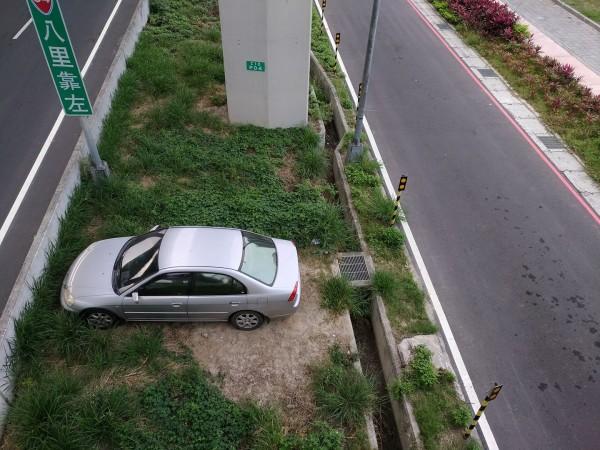 車主自備鐵板「搭橋」將車輛停進高架橋下的分道島中。(擷取自臉書社團「我是五股人」)