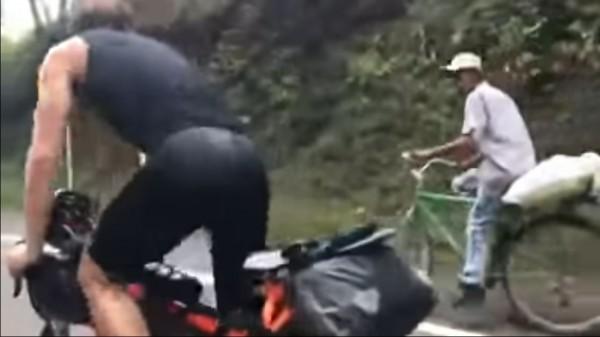 法國運動員正吃力的往上爬,一旁的農民路易斯(圖右)車上雖載貨,尬車時一派輕鬆的完勝專業運動員。(圖擷自YouTube)