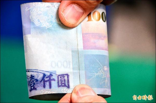 如何辨識真鈔?草屯警分局說,真鈔合併兩頭,圖案線可拼起來。(記者陳鳳麗攝)