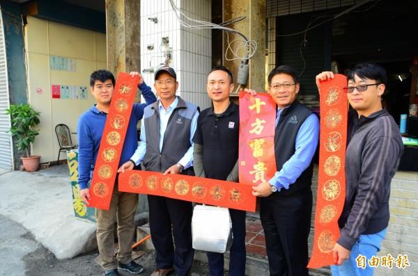 仁德區長郭鴻儀(右二)帶領公所團隊送震災戶春聯與全雞,象徵「起家」。(記者吳俊鋒攝)