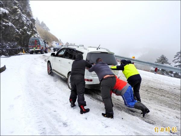 台十四甲線合歡山莊至武嶺陡峭路段,不少車輛縱使加掛雪鏈仍受困,還得煩勞翠峰派出所員警(右)及熱心民眾協助推車。(記者佟振國攝)