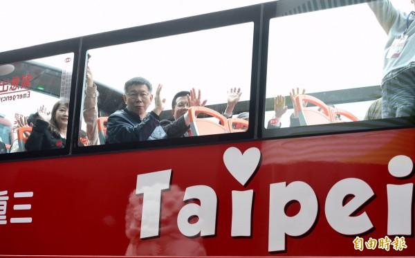 雙層觀光巴士上路,北市長柯文哲在上層向民眾揮手致意。(記者羅沛德攝)