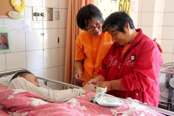 阿鳳姐在伊甸志工陪伴,終於見到臥病在床的丈夫。(記者黃佳琳翻攝)