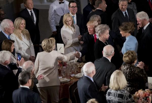 美國總統川普在就職宣誓後於國會山莊出席午餐會,期間與選舉時的民主黨對手希拉蕊握手致意。(美聯社)