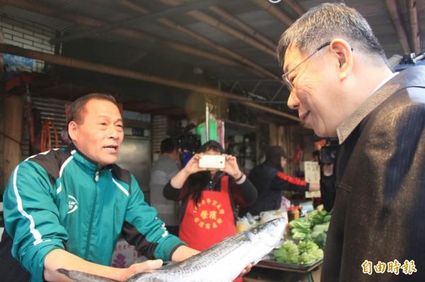 賣魚攤商奉上一隻魚送給柯,祝福柯「步步高升!」(記者陳紜甄攝)