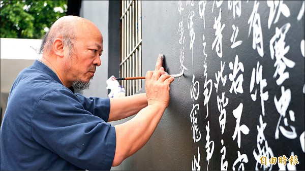 出身屏東大武眷村的書法家章國民在東港共和新村舊眷舍牆上,如行雲流水般寫下「出師表」。(記者陳彥廷攝)