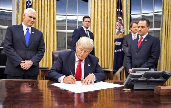 美國總統川普二十三日正式簽署行政命令,退出TPP。圖為川普在白宮簽署後展示該行政命令。(法新社)