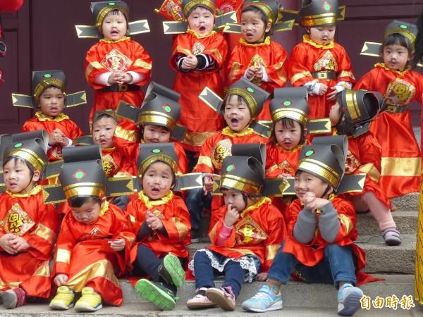 金門一家安親班學童扮演的小小財神爺,遊街到一半在路上小憩,每位「小爺」表情各異,看了令人發噱。(記者吳正庭攝)