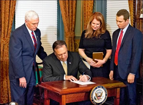 龐皮歐二十三日在宣誓就任中情局長後,簽署宣誓書,站在他左後方的是副總統彭斯,站在他右方的分別是妻子蘇珊與兒子尼克。(歐新社)