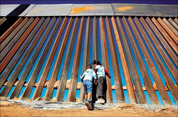 美國新墨西哥州的桑德蘭公園市,去年底有兒童在剛興建完成的美、墨邊界高牆處玩耍。桑德蘭公園市對面就是墨西哥的華瑞茲市。(路透)