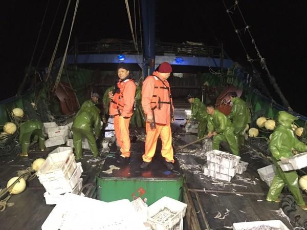 海巡人員登上中國籍漁船檢查。(記者張軒哲翻攝)