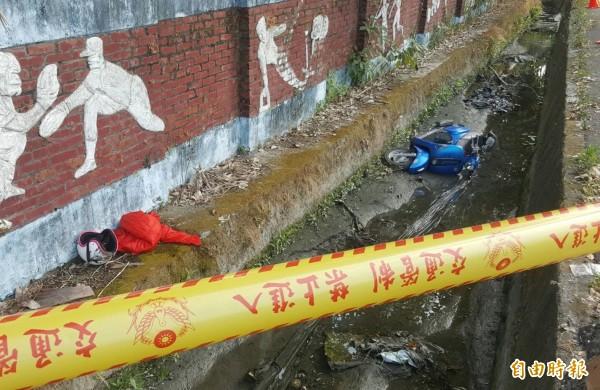 女子衣服及機車被丟在校旁水溝。(記者羅欣貞攝)