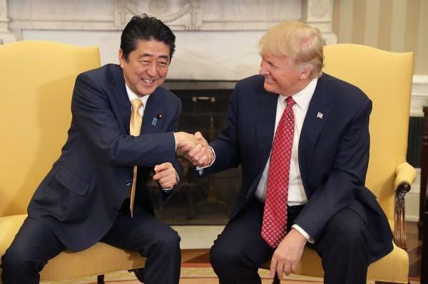 安倍與川普會面,兩人握手長達19秒引發各界熱議。(彭博社)