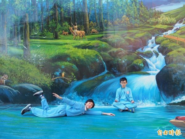 中山國小3D彩繪牆上的瀑布、流水相當逼真,學童陳宥維(右)、鄭竣澤(左)開心模擬打坐、游泳。(記者陳昀攝)