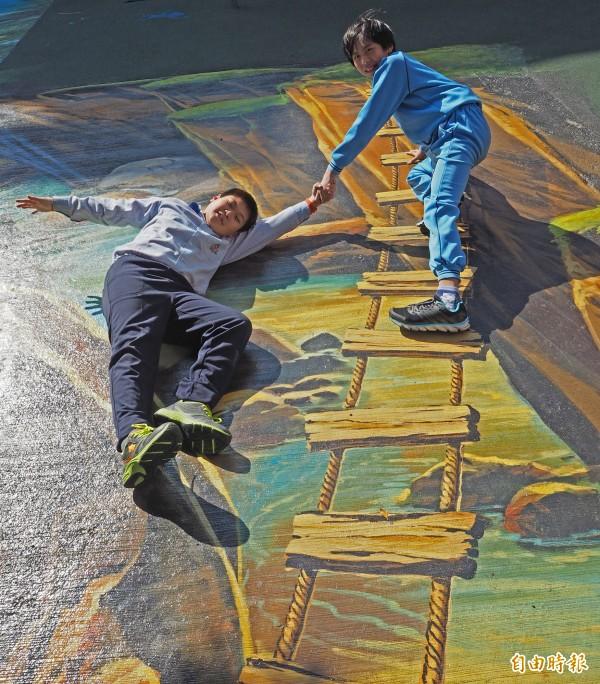 繪製在地面的懸崖和吊橋栩栩如生,學生鄭竣澤(右)、陳煒勳(左)興奮拍照,演技生動。(記者陳昀攝)