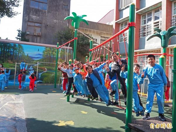 中山國小校長鄭友泰(右三)說,趁著這次換新遊具,把老舊磚牆美化成3D彩繪牆,學童都很開心。(記者陳昀攝)