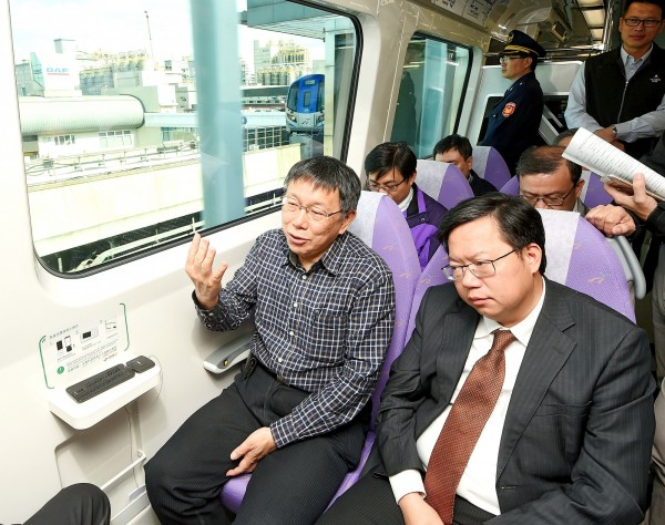 Taipei Mayor Ko Wen-je, left, and Taoyuan Mayor Cheng Wen-tsan ride the Taoyuan International Airport MRT Line from Taipei yesterday. Photo: Fang Pin-chao, Taipei Times