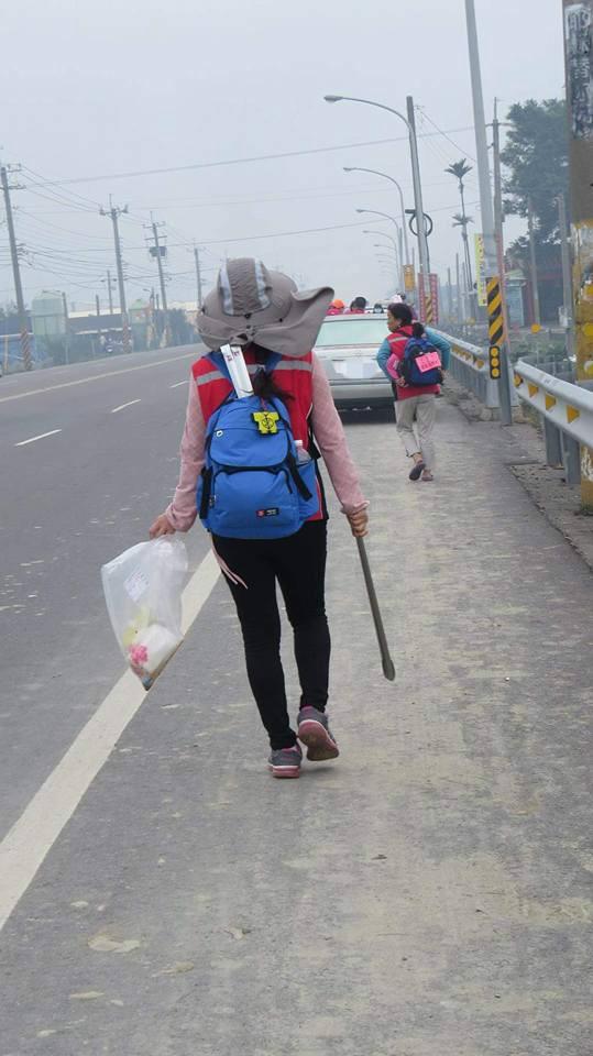 沿途不少信眾自發性地跟在隊伍最後面,手拿垃圾袋及夾子,低頭撿拾信眾們遺留下的垃圾。(擷取自爆料公社)