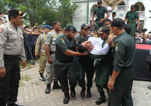 印尼男被打到昏倒。(法新社)