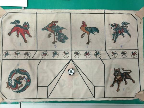 印尼龍虎鬥的賭具骰子與桌布都有龍虎等神獸圖案。(記者周敏鴻翻攝)