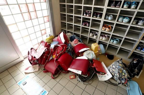 學生當時因強震拋下書包,直接穿著室內鞋就前往避難場所,校舍門口至今仍堆積許多書包及學生的布鞋。(圖擷取自朝日新聞)