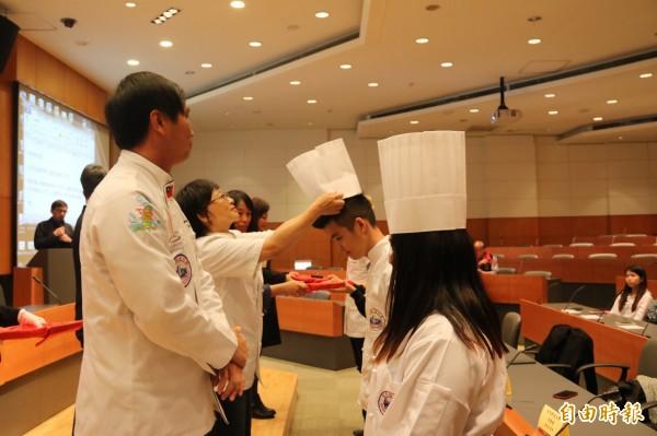 弘光科大海青班開訓,老師贈學生廚師帽、剪刀代表傳承 。(記者張軒哲攝)