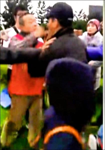 二二八當天中正紀念堂陳抗衝突,統促黨成員李承龍(著紅背心者)被拍到出拳毆打中正一保防組長楊文振。(記者王冠仁翻攝)