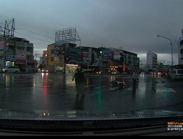 郵差哥(左)青天清晨雨中見車禍,立即伸援手協助指揮交通,感動大批網友。(張姓民眾提供)