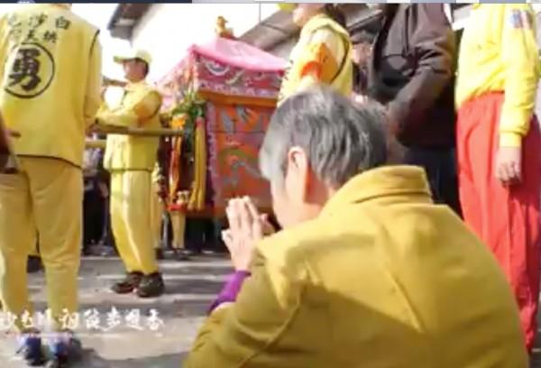 婦人跪地不斷向媽祖神轎磕頭。(翻攝黃朝業臉書)