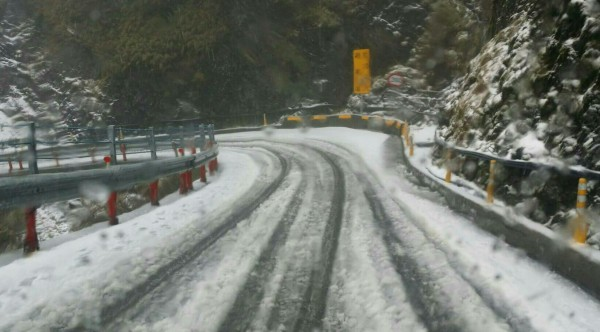 武嶺以上路段路面結冰,車子一定要加掛雪鍊。(仁愛警方提供)