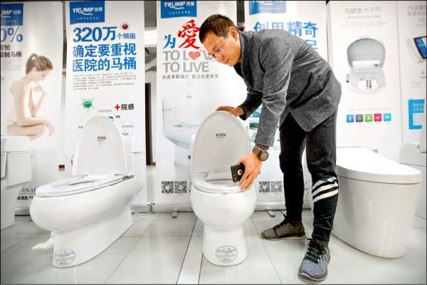 中國近日一口氣初審批准卅八個川普相關品牌商標。圖為以川普姓氏Trump、中文「創普」為品牌的「深圳創普實業公司」共同創辦人,二月展示該公司的馬桶產品。(美聯社)