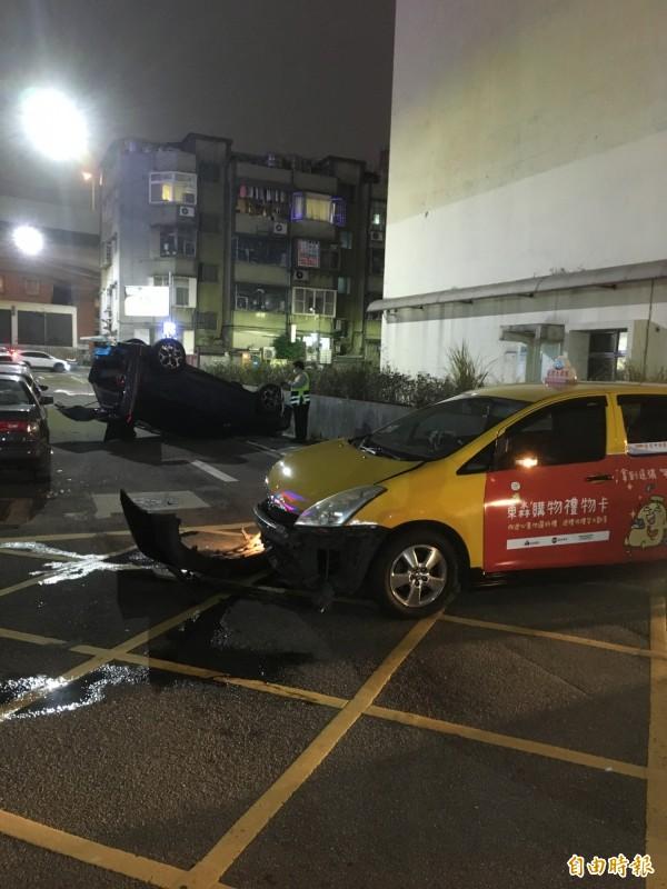 一輛藍色速霸陸「森林人」擦撞計程車,竟意外翻覆。(記者姚岳宏攝)