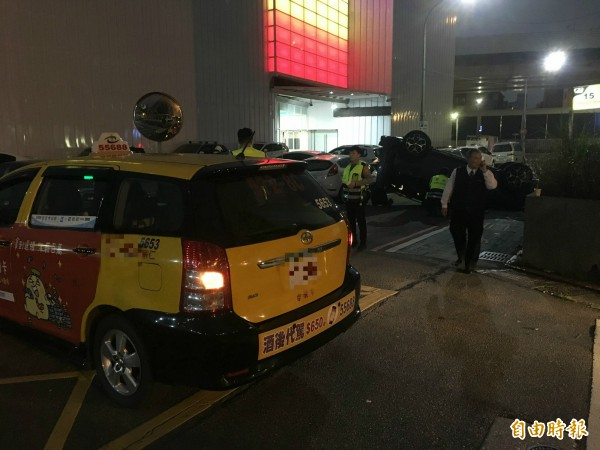 一輛藍色速霸陸「森林人」擦撞計程車,竟意外翻覆;警方到場釐清車禍原因。(記者姚岳宏攝)